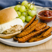 chicken burger on a bun with cheese on a plate