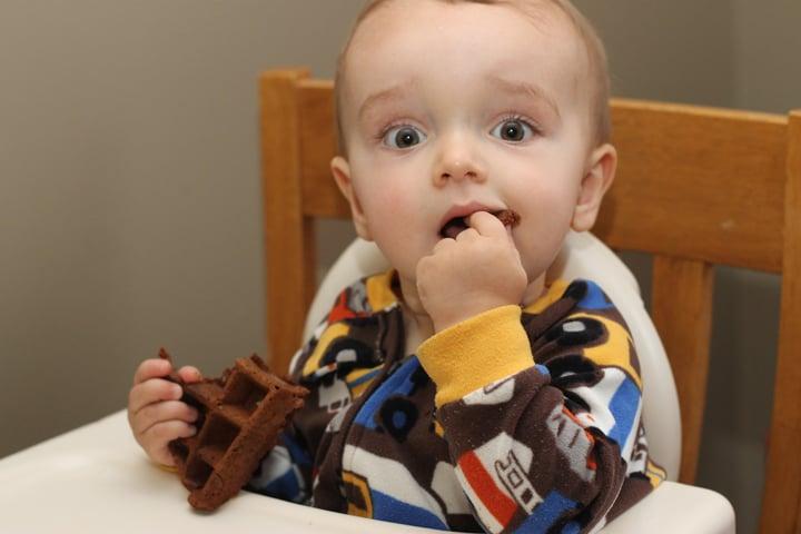 Baby eating a pumpkin waffle