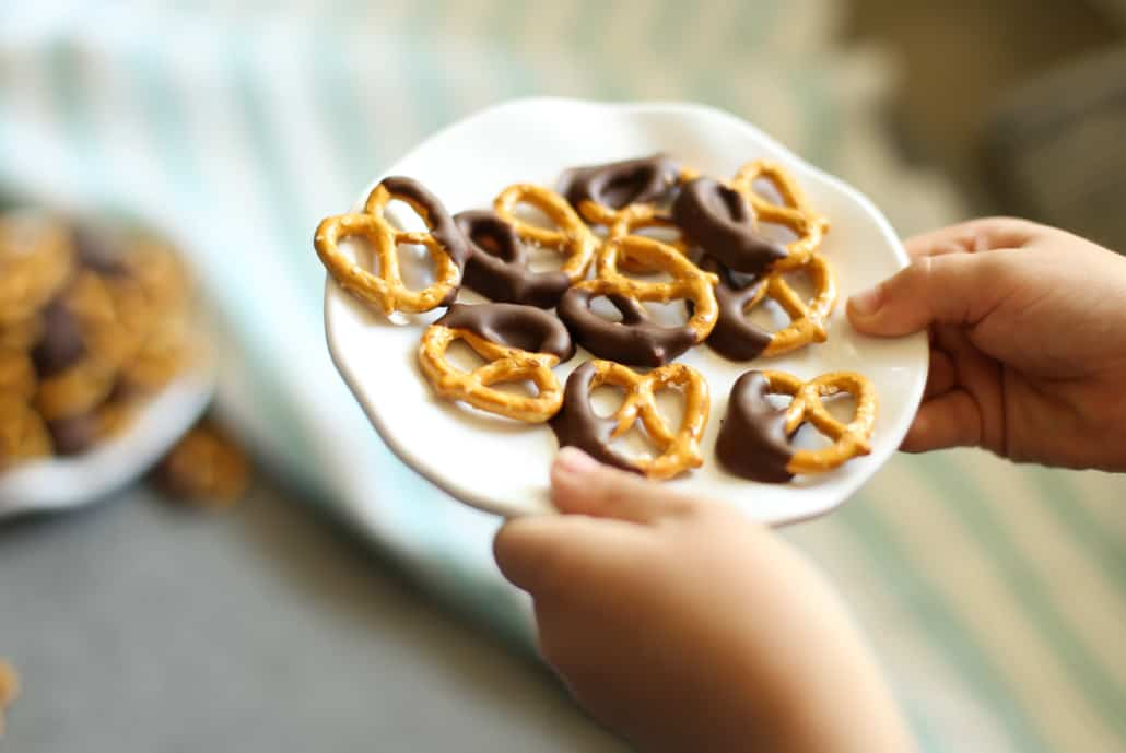 Little hands holding a plate of chocolate covered pretzels