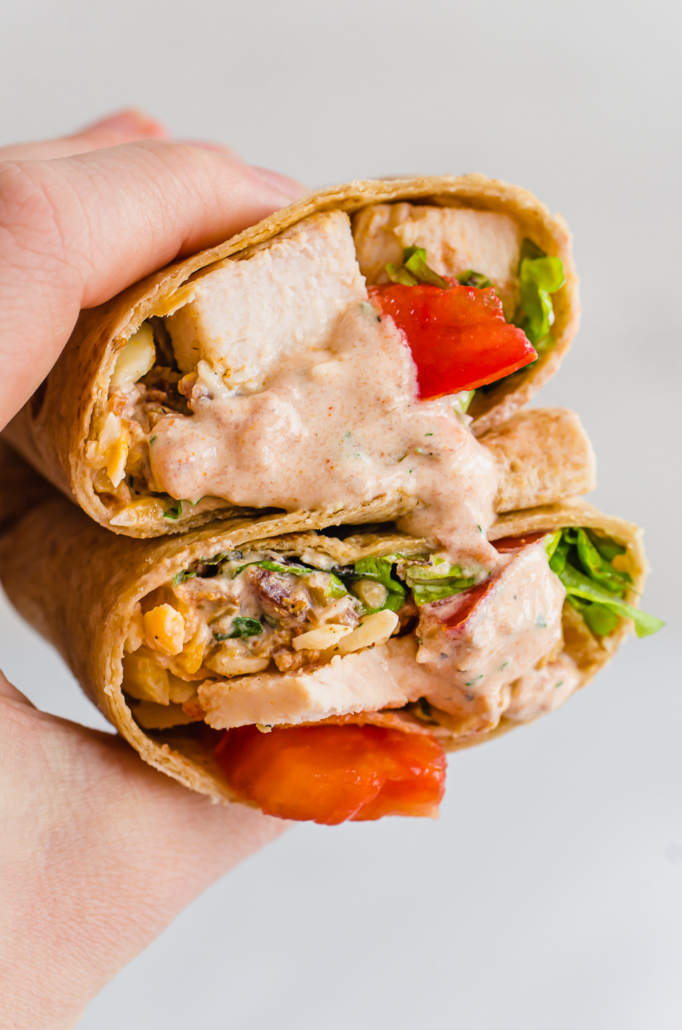 Southwest Chicken wraps, cut in half and being held in a hand
