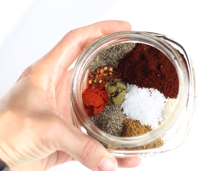 A hand holding a jar of taco seasoning mix