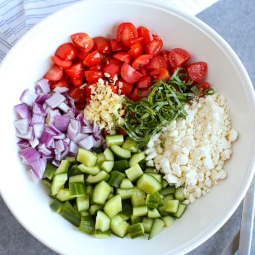 chopped cucumber, red onion, tomatoes, basil, garlic and crumbled feta in a white bowl