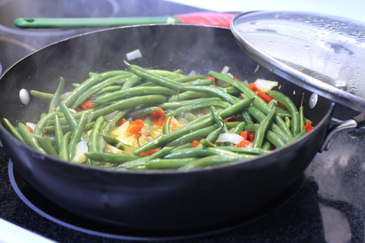 Have a picky eater in your house? Try these crowd-pleasing green beans. A touch of bacon grease and a combo of fresh veggies makes a delicious side dish!