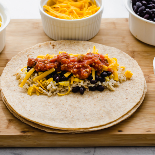 vegetarian lunch wraps on a wooden cutting board with small bowls of corn, salsa, and rice