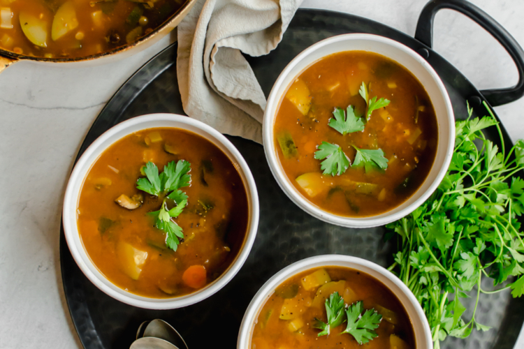 Large pot of vegetable soup with three bowls of vegetable soup. Spoons and napkins and fresh herbs on the side.