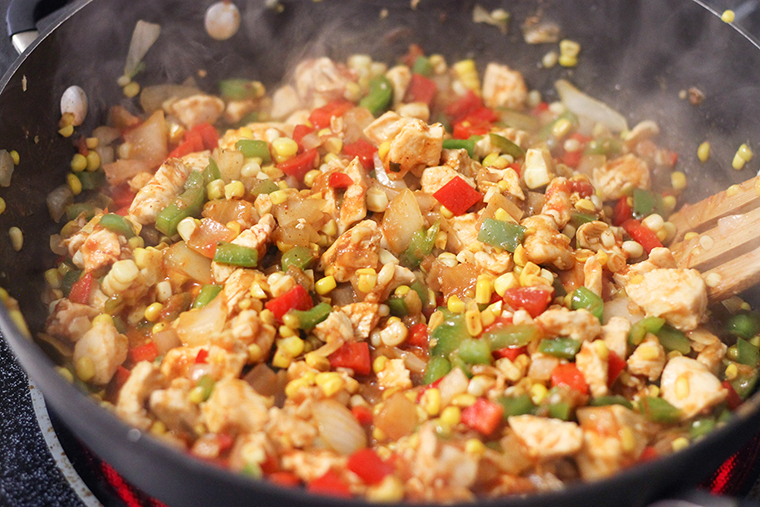Chicken and vegetables cooking in a skillet