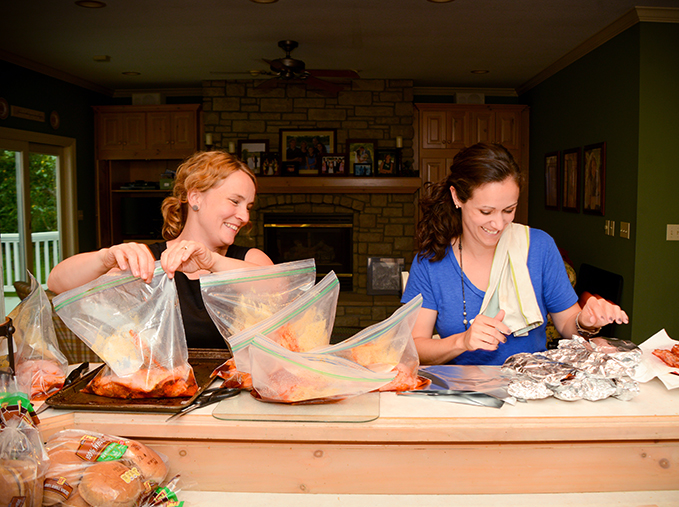 Two women packaging freezer meals