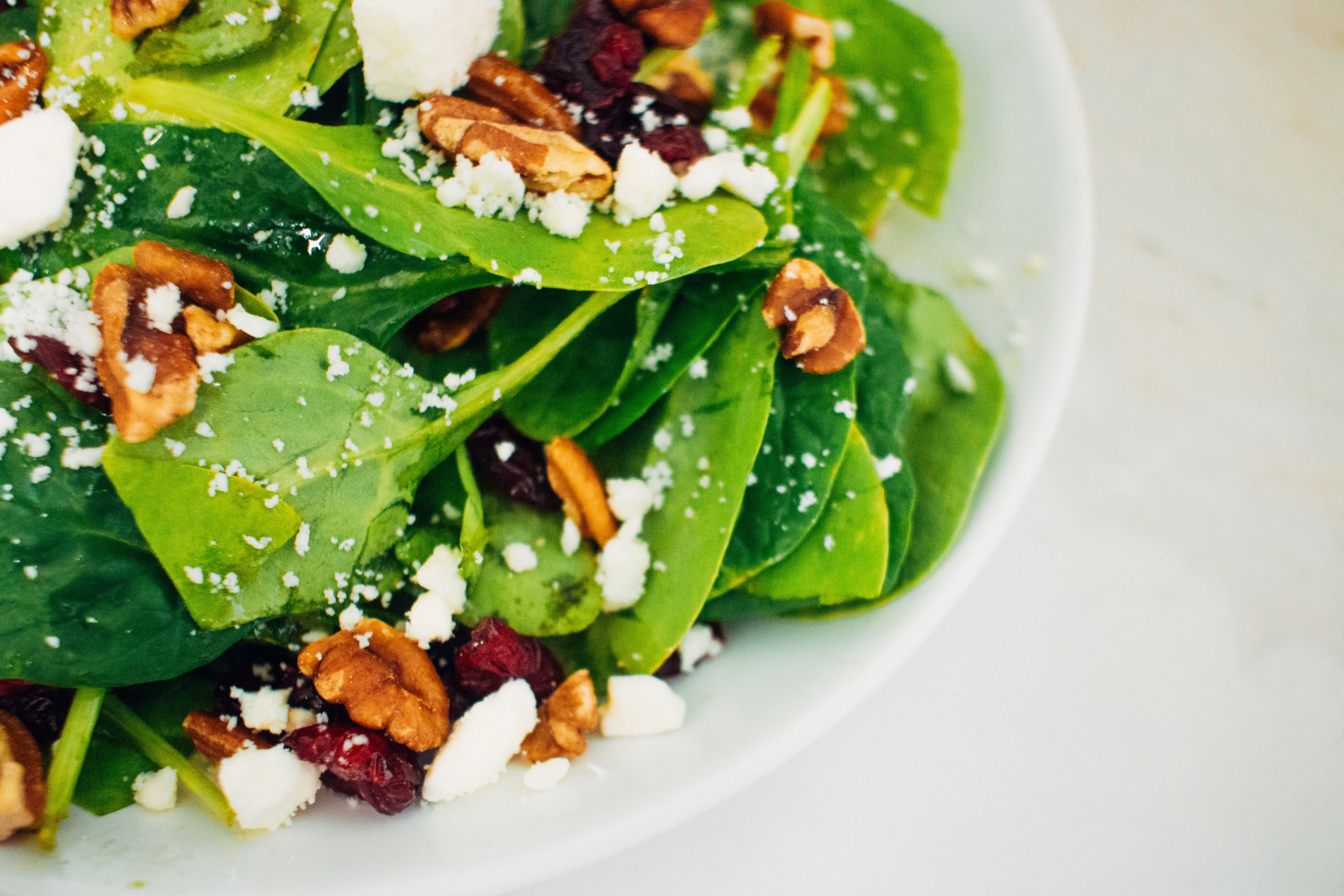 Cranberry Spinach Salad with Creamy Citrus Dressing in white bowl