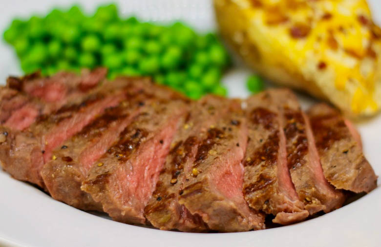 Sliced steak on a plate with peas