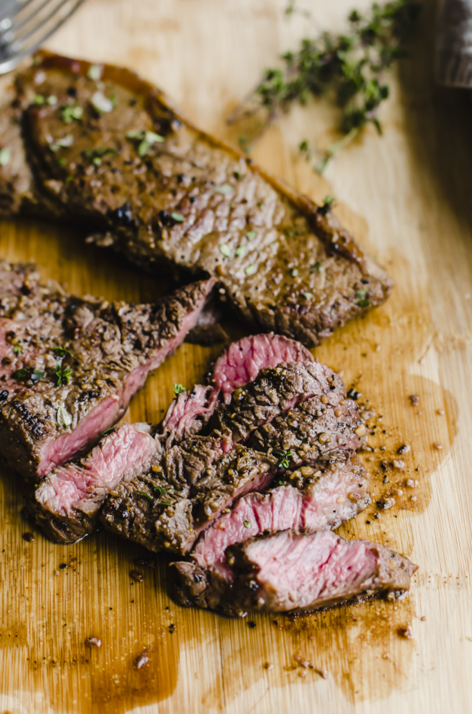 seasoned cooked steak that is sliced on a wooden cutting board