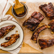 slow cooked ribs on a cutting board with extra sauce on the side