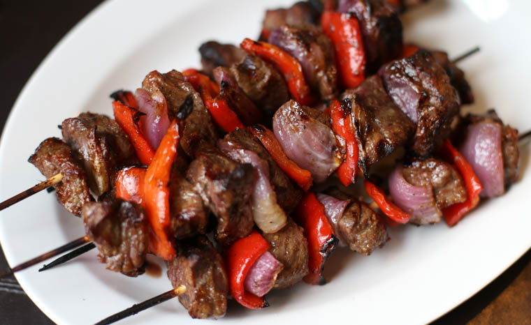 Cooked sirloin steak kebabs on a white plate