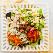 cobb salad on a white plate with yellow napkin