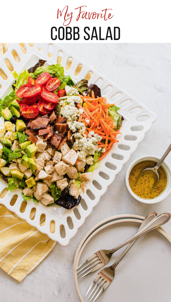 cobb salad on a white plate with yellow napkin and dressing on the side