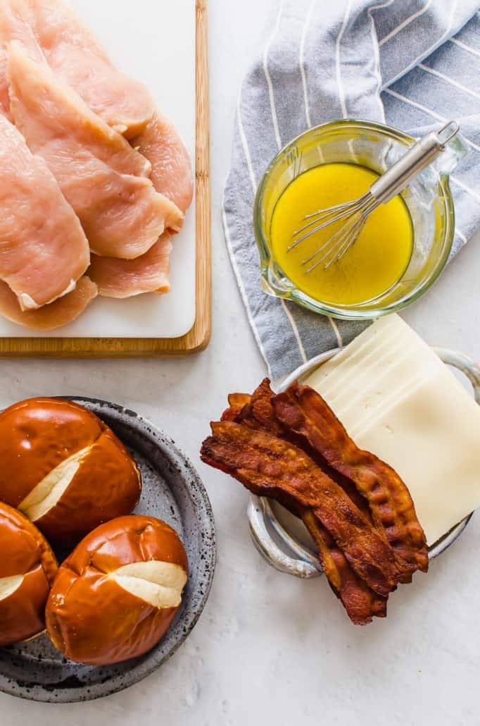chicken, pretzel buns, bacon, cheese, and Honey Dijon Sauce on a counter