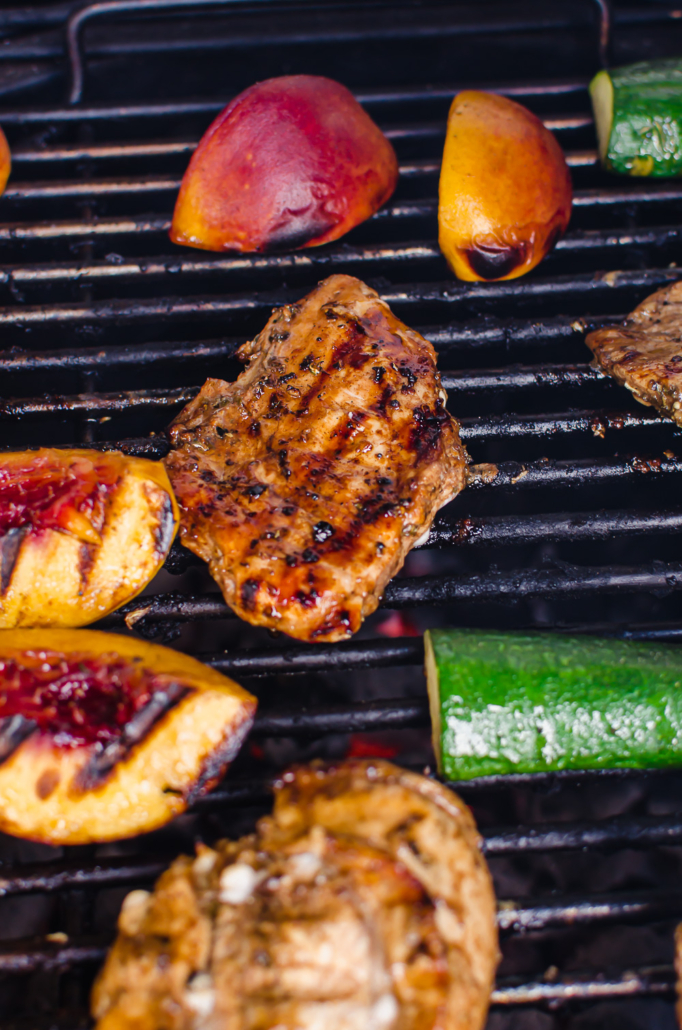 grilled balsamic herb chicken on the grill with zucchini and peaches