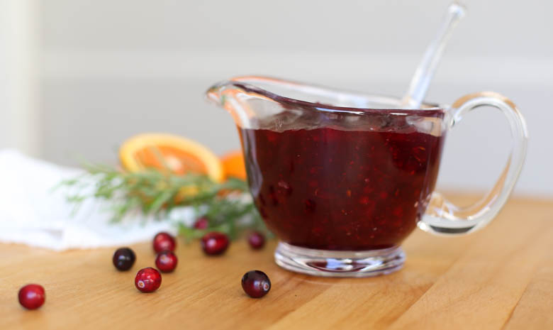 homemade cranberry sauce in a glass bowl with fresh cranberries, orange, and rosemary as garnish