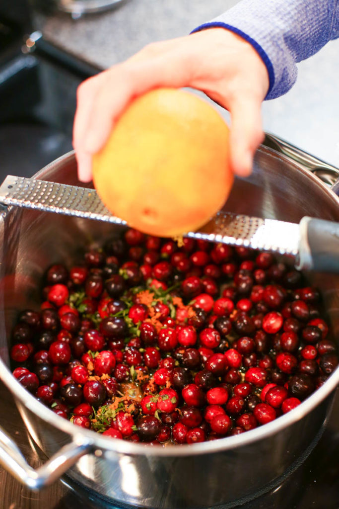 zesting orange over homemade cranberry sauce in a pot