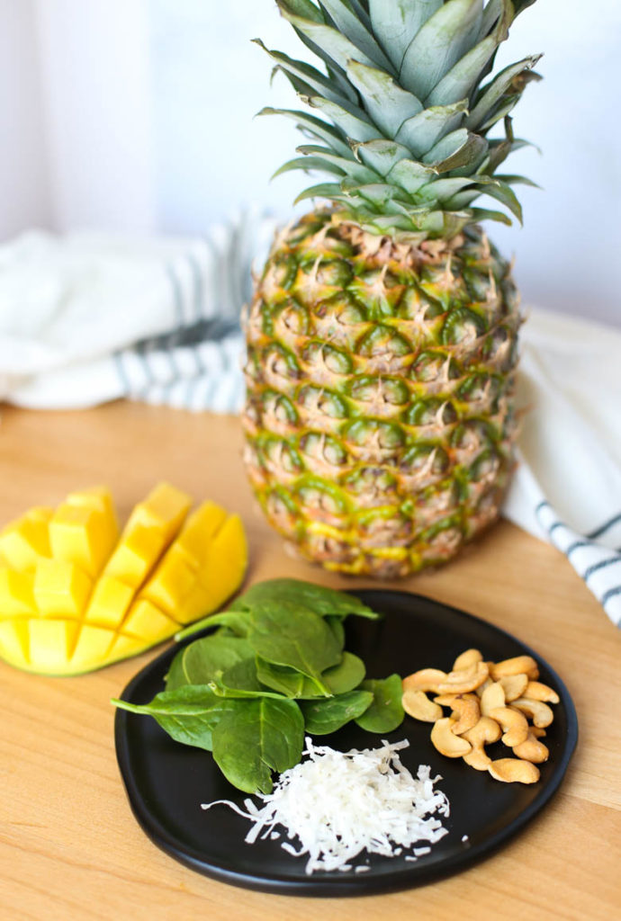 pineapple, mango, spinach, cashews on cutting board