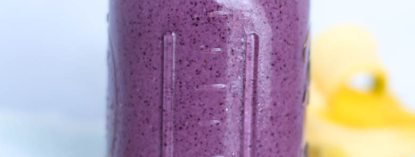 blueberry smoothie in mason jar with straw