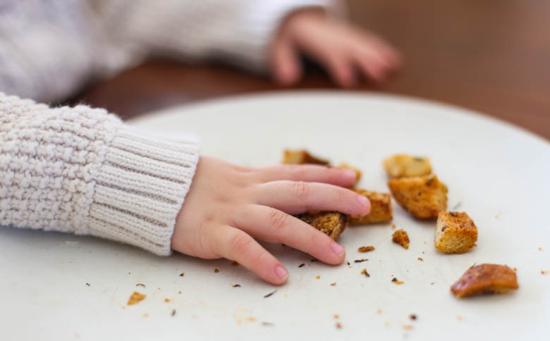 Children's hands picking up homemade croutons