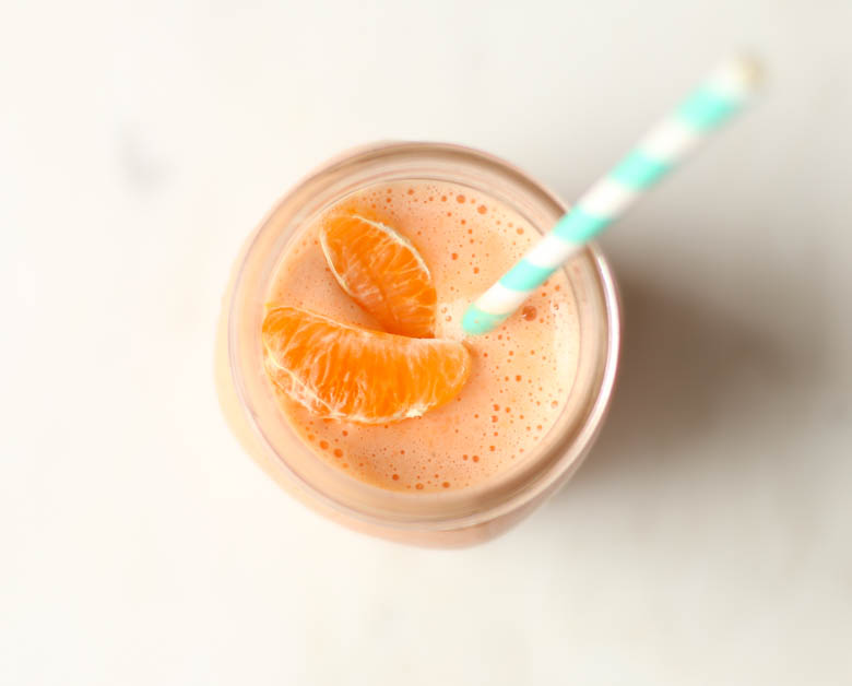 Orange smoothie in mason jar with straw