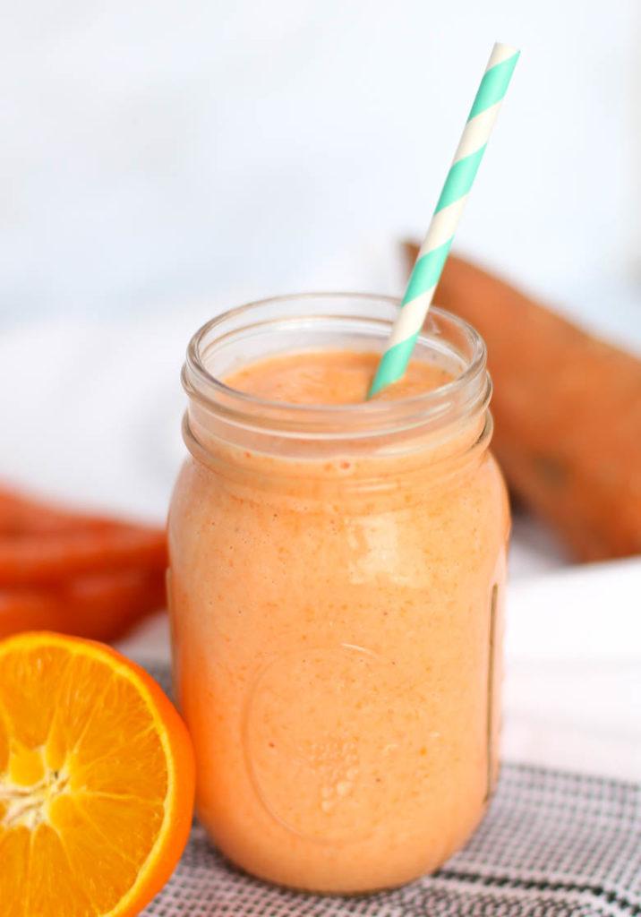 Orange smoothie in mason jar with straw