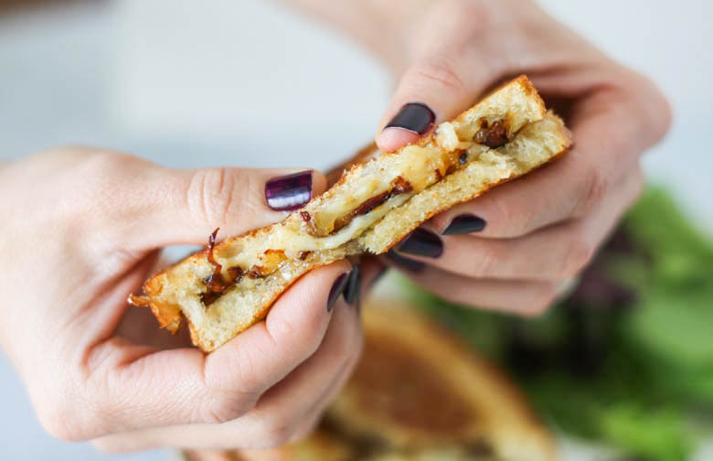 Hands holding a Gourmet Grilled Cheese Sandwich