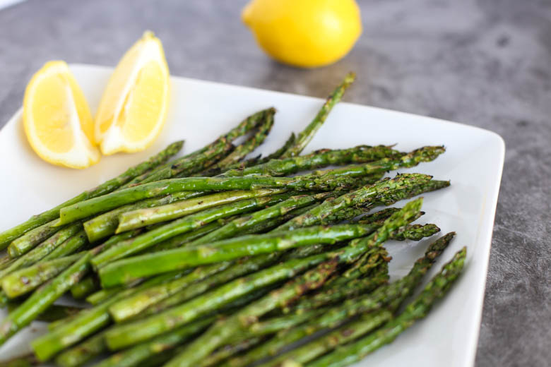 Grilled asparagus on a white plate with lemons