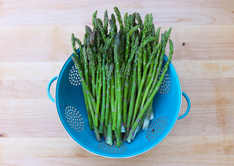 Fresh asparagus in a blue colander