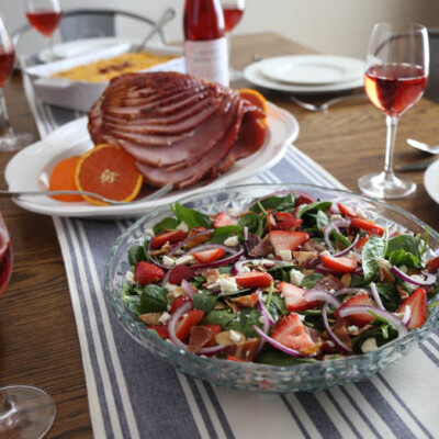 Easter lunch on table with salad, ham, hash brown casserole, and wine