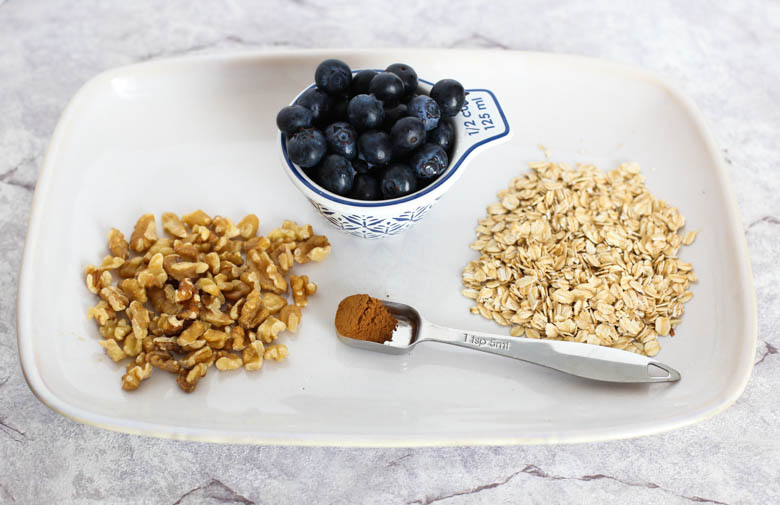blueberries, oats, walnuts, and cinnamon on a white platter