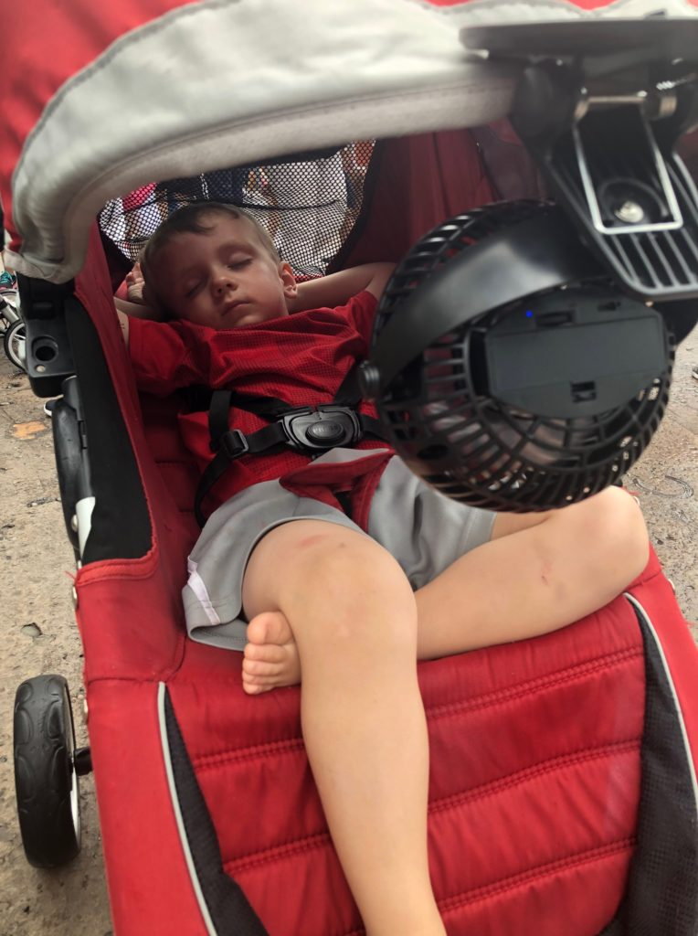 Sleeping boy with clip on fan on stroller