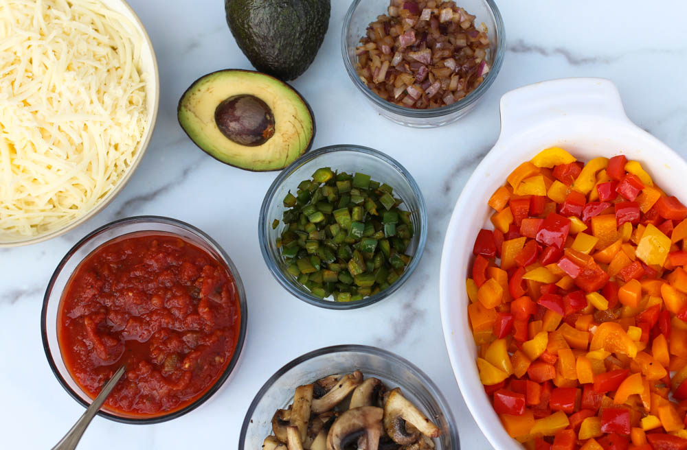 a variety of add-in options for freezer-friendly breakfast burritos, including sauteed peppers, red onions, mushrooms, salsa, Monterey Jack cheese, and avocado