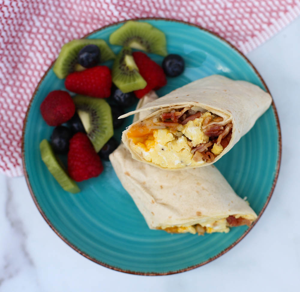 breakfast burritos on a plate with fruit