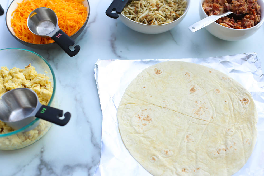breakfast burrito assembly line with eggs, cheese, hash browns, and bacon