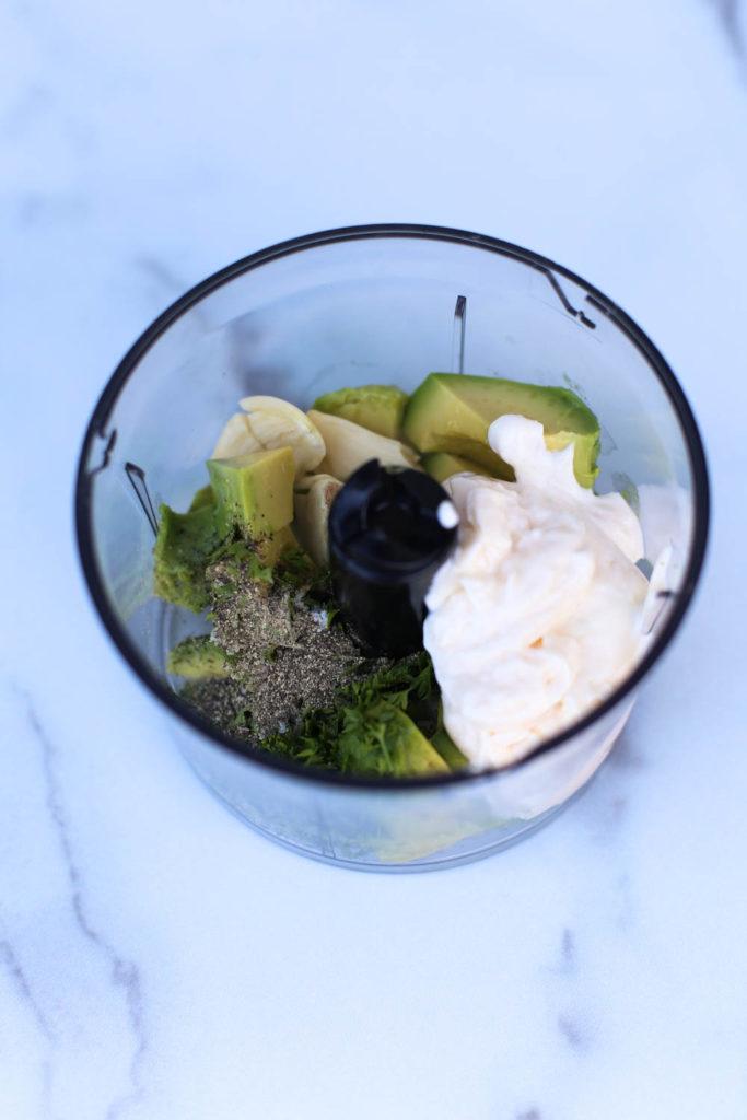 Homemade Avocado Garlic Aioli ingredients in a food processor bowl
