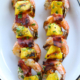 bacon-wrapped shrimp kabobs on white platter