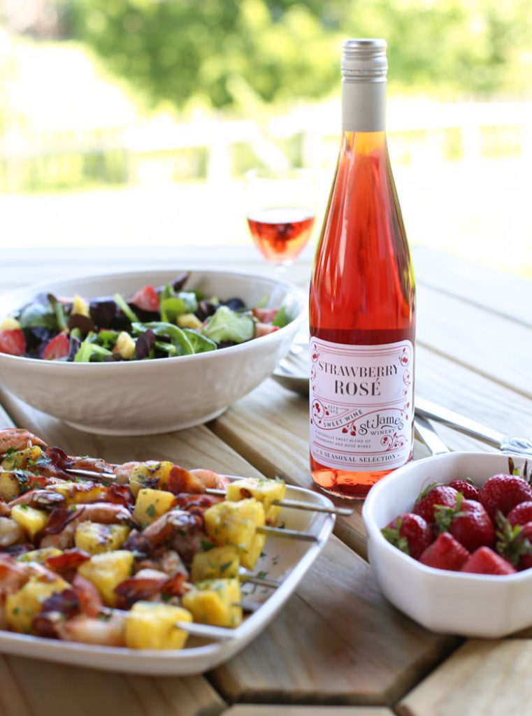 bacon-wrapped shrimp kabobs, a bottle of St. James Winery Strawberry Rose, strawberries, and green salad on a picnic table