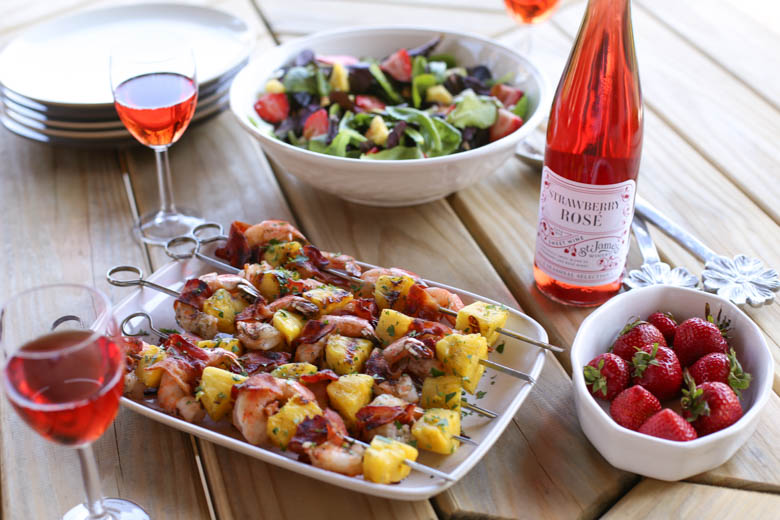 Strawberry avocado salad, kabobs, strawberries on a wooden table.
