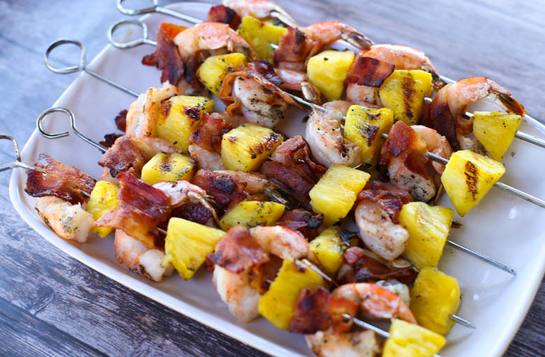 Bacon-Wrapped Shrimp and Pineapple Kabobs on a white platter on a table