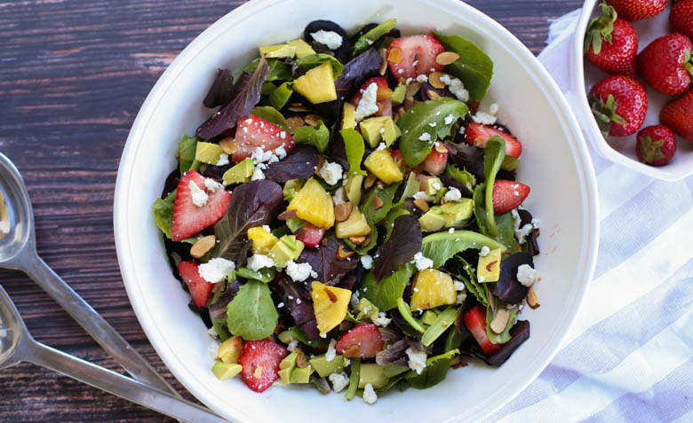 strawberry avocado salad in a white bowl on a table