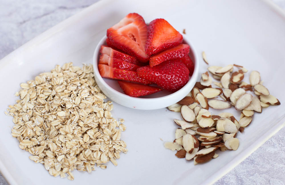 strawberries, almonds, oats on a white platter
