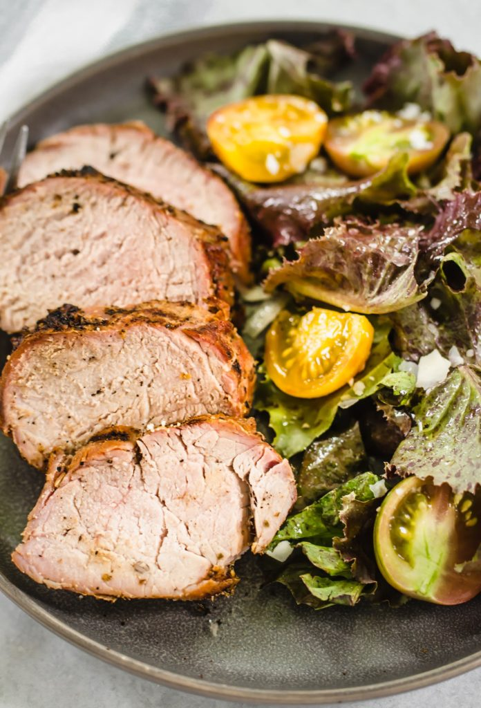 Grilled pork tenderloin on a plate with salad