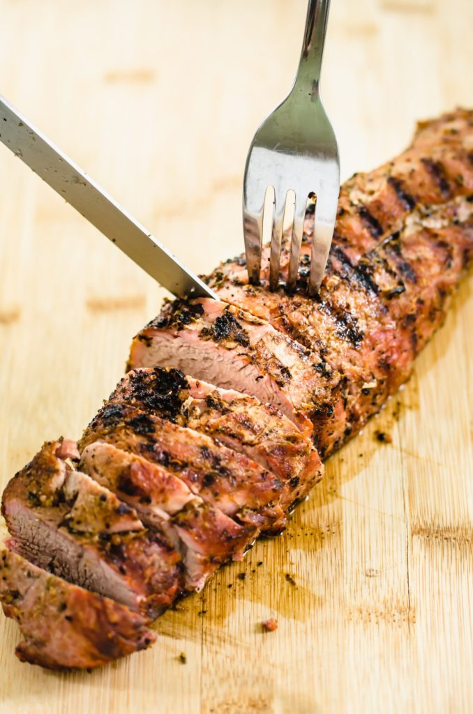 grilled pork tenderloin sliced on a cutting board