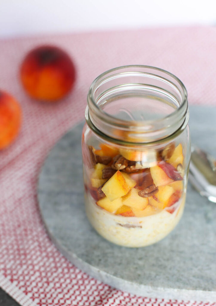 Overnights Oats with milk, oats, flax, peaches, cinnamon, vanilla, and pecans in a mason jar.