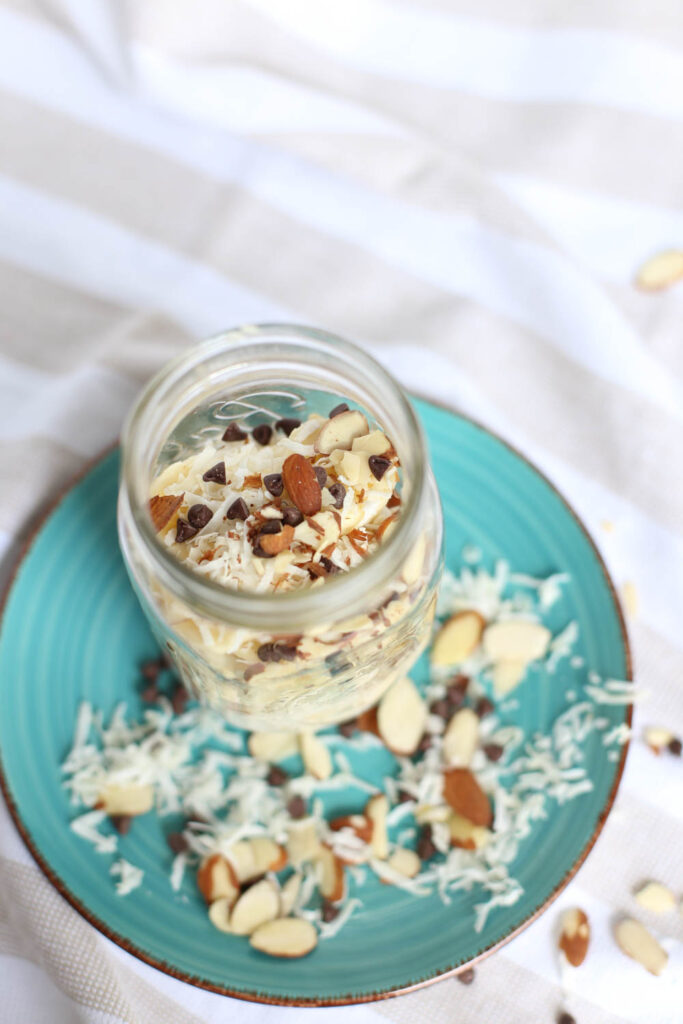 Almond Joy Overnight Oats in a mason jar on top of turquoise plate. Shredded coconut, sliced almonds, and chocolate chips are scattered around.