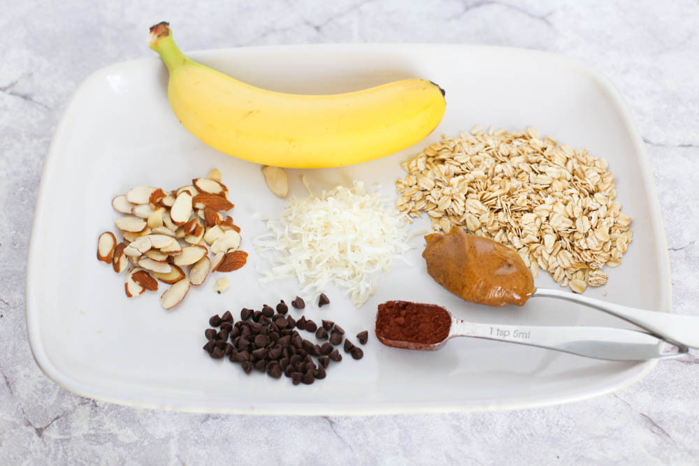 Almond Joy Overnight Oats ingredients on a white plate. Includes bananas, oats, almond butter, cocoa, chocolate chips, shredded coconut, and sliced almonds.
