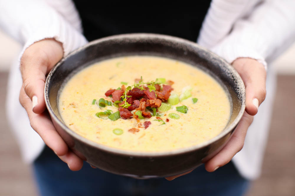 Hands holding a brown bowl of Slow Cooker Cheddar and Bacon Potato Soup.