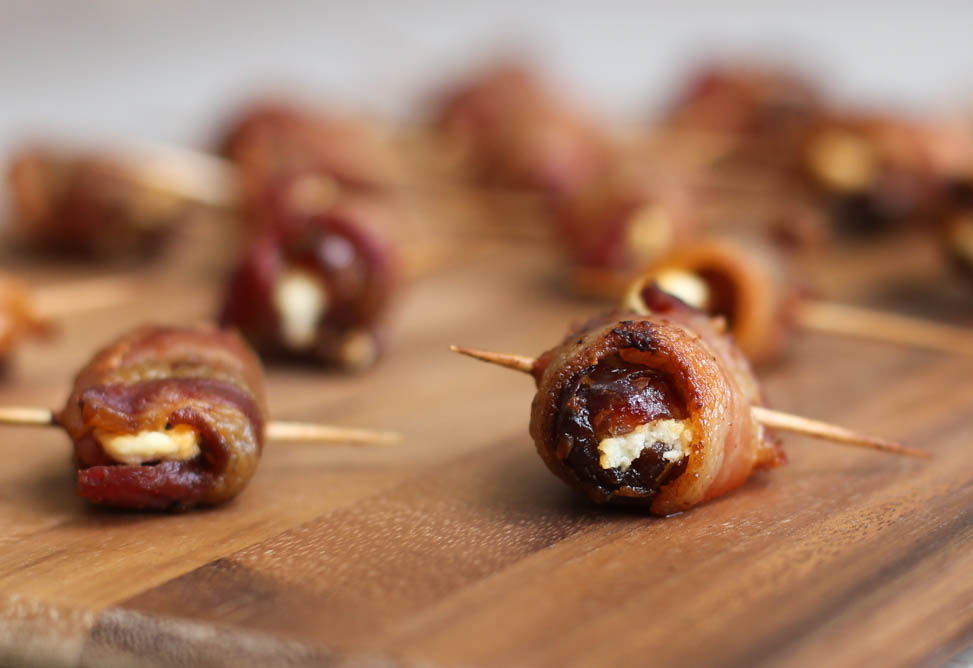 Bacon-Wrapped Dates with Goat Cheese on a cutting board